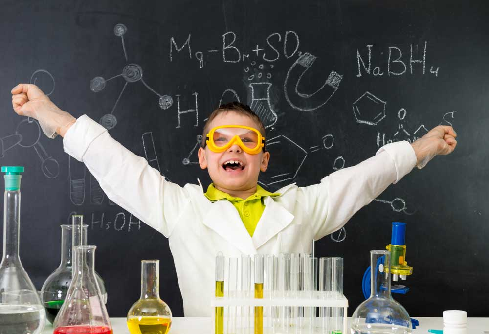 excited schoolboy with hands up in chemistry lab made a discovery