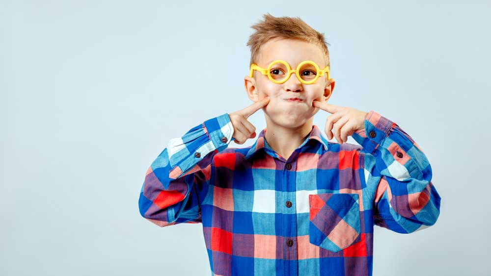 Little boy wearing colorful plaid shirt, plastic glasses having fun in the studio