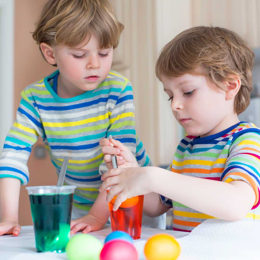 Cute blond little kids coloring eggs for Easter holiday in domestic kitchen, indoors. Children having fun and celebrating feast.