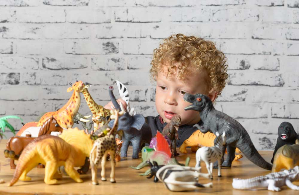 a little child plays with toys animals and dinosaurs