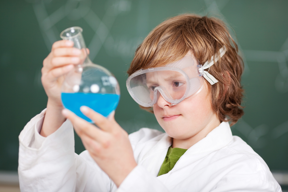 Young boy performing chemistry experiments at the lab